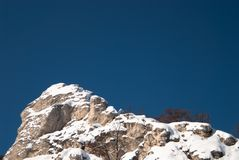 Snow-covered high rocky cliff against clear blue s Royalty Free Stock Image