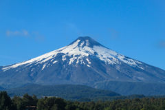Snow covered hight volcano summit above the forest Royalty Free Stock Photo