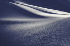 A snow covered hill with a strong contrast of light and shadow. A texture of a small, snow covered hill in a cold environment with a contrast of light and royalty free stock photos