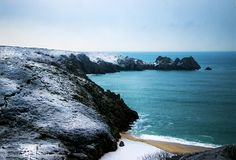Snow covered hills and aquamarine, crystal clear waters of Porthcurno Beach in Cornwall, England Stock Image