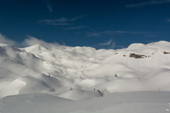 Snow covered hills. Hills covered in snow with blue sky and blown clouds Stock Image