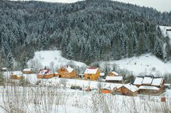 Snow-covered hills, forest and houses in the distance. Winter landscape.  stock images