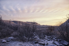 Snow-covered hills and the forest at sunset. Close to the railway and the river Royalty Free Stock Image