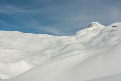 Snow covered hills. Hills covered in snow and rocks showing underneath the mountain top Royalty Free Stock Photos