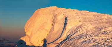 Snow covered hillside closeup in wintertime. mountain. Christmas. Panorama of snow dune close up on a background of blue sky. At the bottom of the cloud. Sunset Royalty Free Stock Image