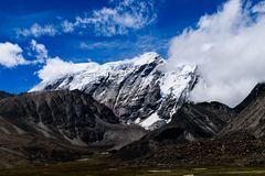 Snow Covered Himalayan Mountain Range With Clouds Originating From It stock photos