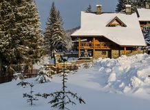 Snow-covered hotel complex in the beautiful winter Carpathians,. UKRAINE – February, 2017: In the foreground are fir trees covered with snow, in the background Royalty Free Stock Photo
