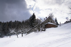 Snow covered house in a frosty mountains country in sunny day Stock Photo