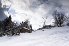 Snow covered house in a frosty mountains country in sunny day Stock Photos