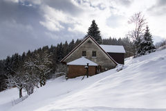Snow covered house in a frosty mountains country in sunny day Stock Photography