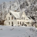 Snow-covered house in the mountains stock photo