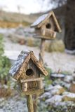 Snow Covered Houses. Two snow covered bird boxes, one in focus, one out royalty free stock photo
