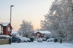 Snow covered houses and cars on a street in London stock photos