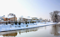 Snow covered houses by a river Stock Image