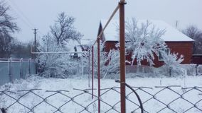 Snow-covered houses and a fence in the village. Snow-covered houses, trees and a fence in the village Royalty Free Stock Photos