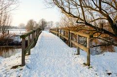 Snow-covered houten voetgangersbrug in de winter stock afbeelding