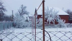 Snow-covered huizen en een omheining in het dorp Royalty-vrije Stock Foto's