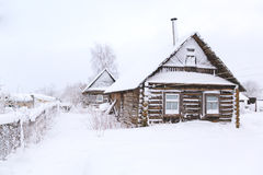 Snow-covered hut old. Old abandoned wooden hut uninhabited under the snow Stock Photo