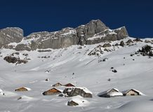 Snow covered huts and mountains Stock Images