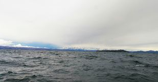 Snow covered illampu with titicaca lake stock photography