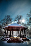 Snow covered Kiosk in the park with blue sky. As background in winter time and sun pointing towards the camera Stock Photography