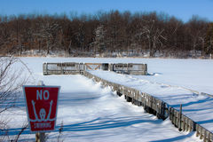 Snow Covered Lake. A photo of a snow covered lake on a winter day with bright blue sky. In the foreground is a No Swimming sign Royalty Free Stock Images