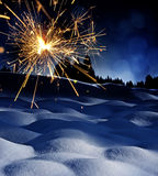Snow covered landscape and sparkler - christmas Stock Photos