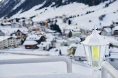 Snow covered lantern between two railings with mountain village houses on background. Snow covered lantern between two railings with mountain village houses on Royalty Free Stock Images