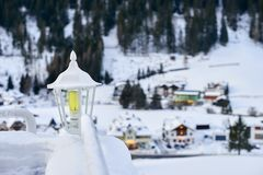 Snow covered lantern between two railings with Tyrol Alps ski resort on background. Snow covered lantern between two railings with Tyrol Alps ski resort on Royalty Free Stock Images