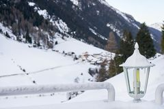Snow covered lantern between two railings with Tyrol Alps ski resort on background. Snow covered lantern between two railings with Tyrol Alps ski resort on Stock Photos