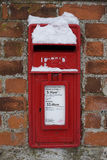 Snow Covered Letter Box. A red postbox set in a brick wall after a snowfall Stock Photography