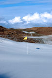 Snow covered links golf course with yellow flag Royalty Free Stock Image