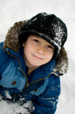 Snow covered little boy. Six year old boy out playing in the winter snow Stock Image