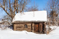 Snow-covered little typical wooden rural house. Snow-covered little typical wooden russian rural house in sunny winter day in small village in Smolensk region of Royalty Free Stock Photography