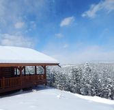 Snow Covered Log Cabin Looking Over The Winter Horizon Royalty Free Stock Photos