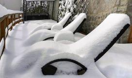Snow-covered loungers. Snowalpi dolomiti royalty free stock photo