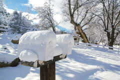 Snow Covered Mailboxes 01. A winter and snowy rural scene featuring an pair of post supported and snow covered mailboxes. The background features a slight hill Royalty Free Stock Images
