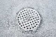 Snow covered manhole cover Royalty Free Stock Photography