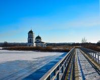 Snow-covered meer met een metaalbrug naar kerk stock afbeelding