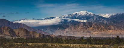 Snow Covered Mount San Jacinto. Beautiful snow-covered Mount San Jacinto rises above the Coachella Valley and San Gorgonio Pass Wind Farm, Palm Desert Royalty Free Stock Image