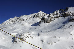 Snow covered mountain. Closeup view of a snow covered mountain with blue sky overhead stock photos