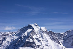 Snow-covered mountain in Alps. Swiss alps mountain in winter with clear blue sky Stock Photo