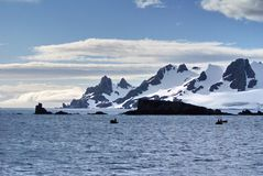 Snow covered mountain in Antarctica with inflatable boats in front Royalty Free Stock Photography