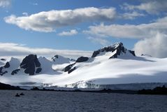Snow covered mountain in Antarctica with inflatable boats in front Stock Photos