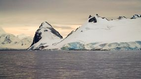 Snow covered mountain landscape in Antarctica around Cuverville Island. Royalty Free Stock Photo