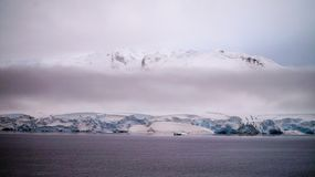 Snow covered mountain landscape in Antarctica around Cuverville Island. Royalty Free Stock Photos