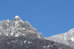 Snow-covered mountain peak against blue skies. Iron cross and snow on top of Mount Sassariente against blue skies Stock Images
