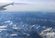 Snow-covered mountain peaks with altitude aircraft. Royalty Free Stock Photos