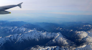 Snow-covered mountain peaks with altitude aircraft. Royalty Free Stock Images
