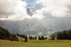 Snow covered mountain peaks and cable cars in Grindelwald, Switzerland Stock Photography